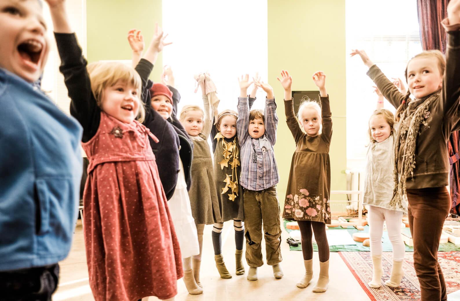 Kinder die die Arme hochwerfen