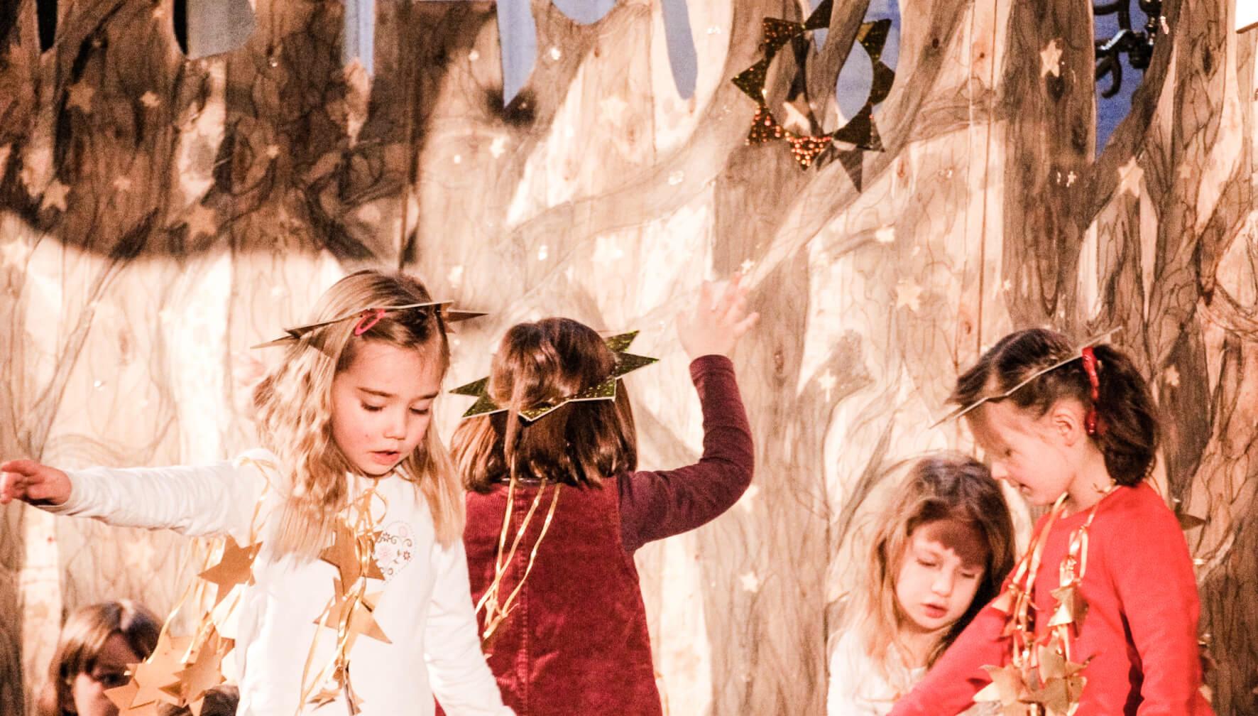 Kinder als Sterne verkleidet tanzen