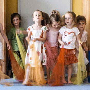 Kinder tanzen mit bunten Tüchern